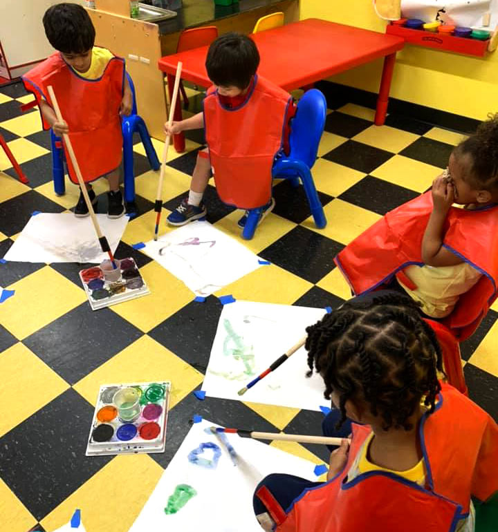 Children painting with large brush at Robin's Nest Learning Center in Carbondale, Illinois