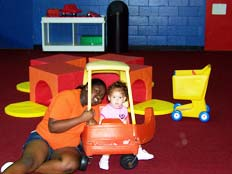 staff member playing with girl in cozy comfort car