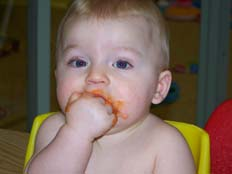 Nursery boy eating with hands